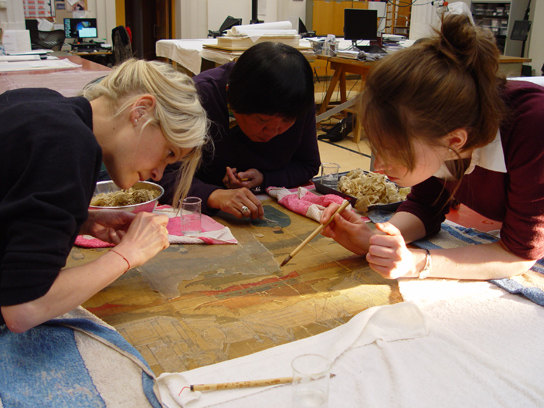 Mrs Qiu with her two assistants, Valentina Marabini and Carol Weiss, removing the painting's old backing papers