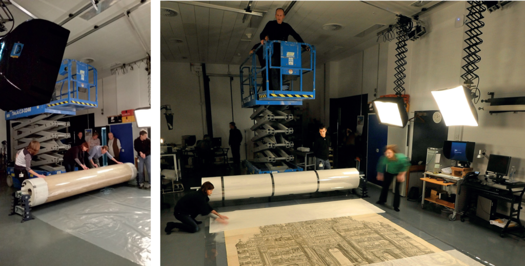 Carefully unrolling the print ready for photography, with the mobile extendable work platform in place.