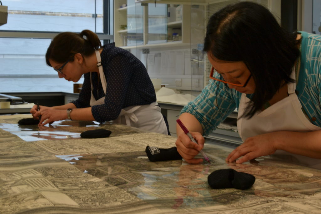 Conservators Emma Webb (left) and Megumi Mizumura (right) mapping out damage to individual pages of Dürer's Triumphal Arch.