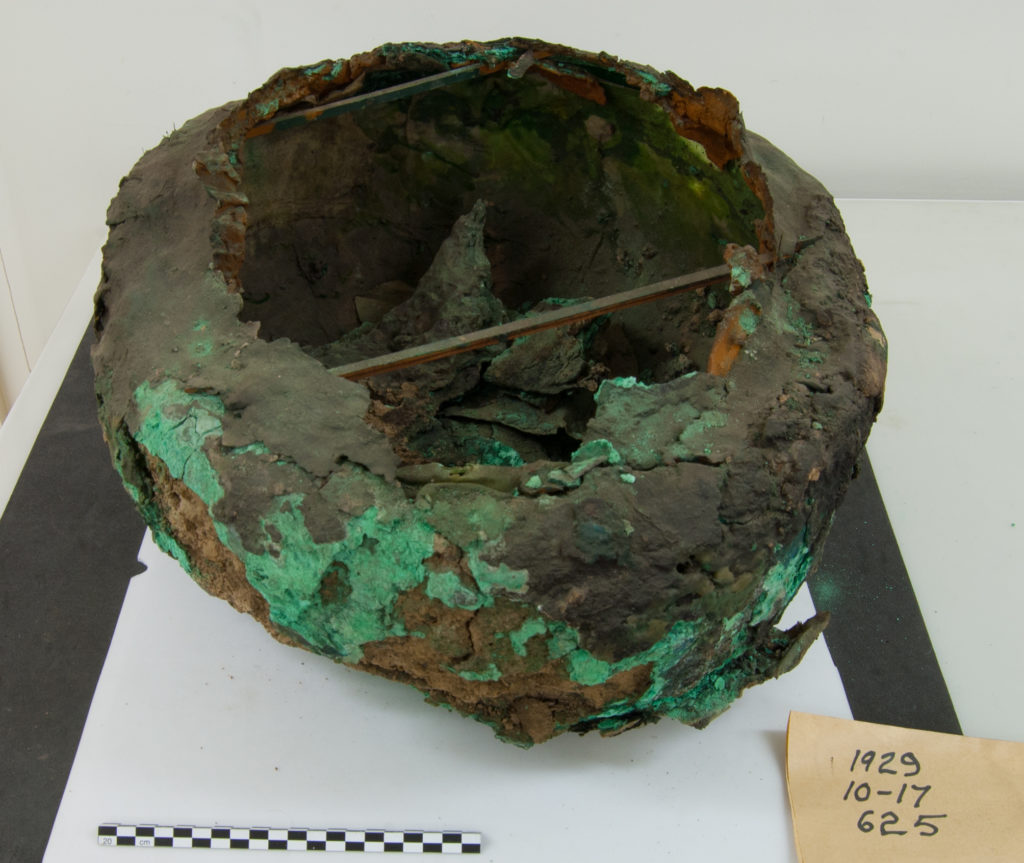 Cauldron. The rim is detached. The wooden supports across the interior were probably added at the same time that the rim was repaired.