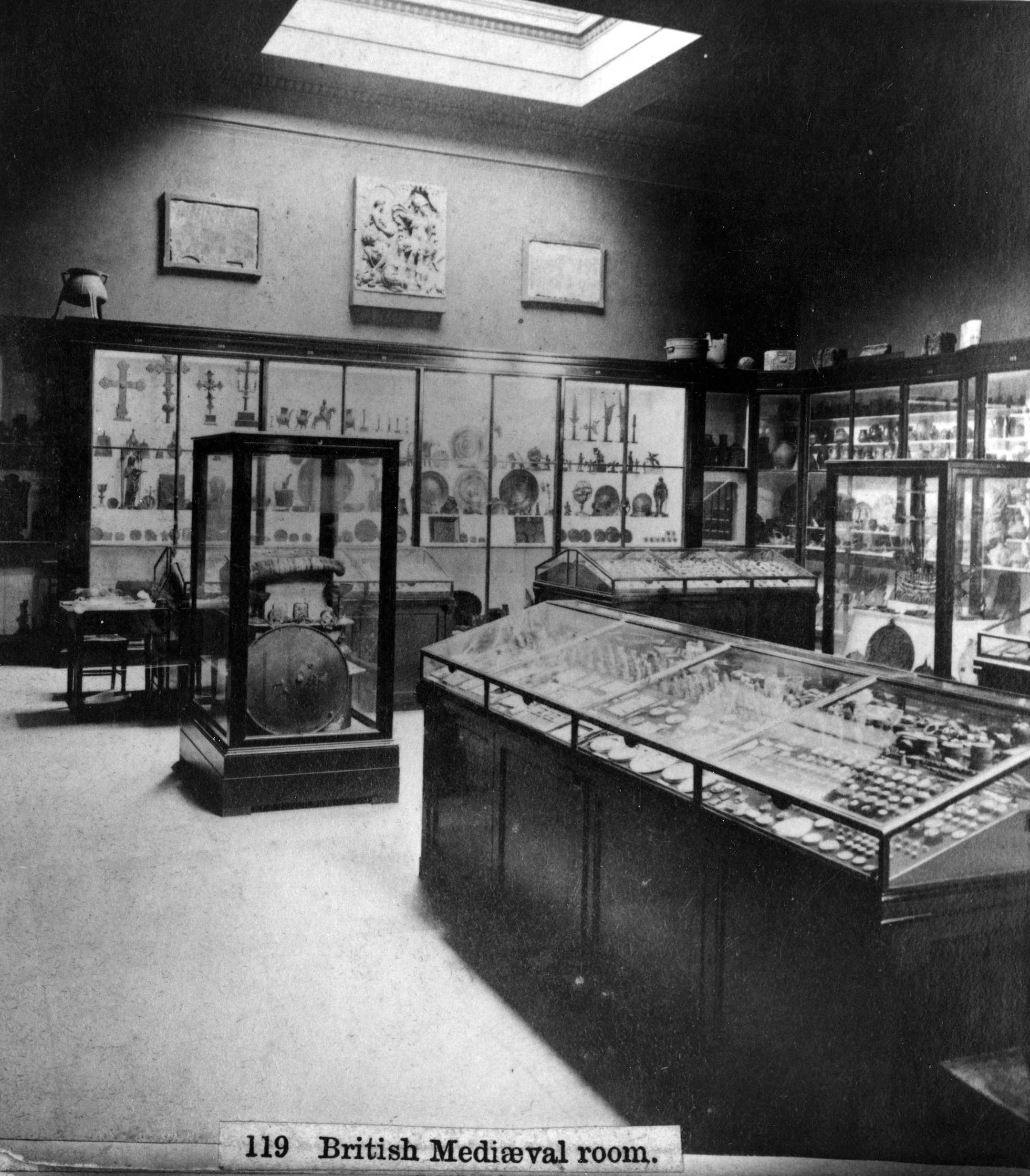 Black and white photograph of the Museum's Medieval room in 1875, showing a display case in the centre of the room containing the Lewis Chessmen.