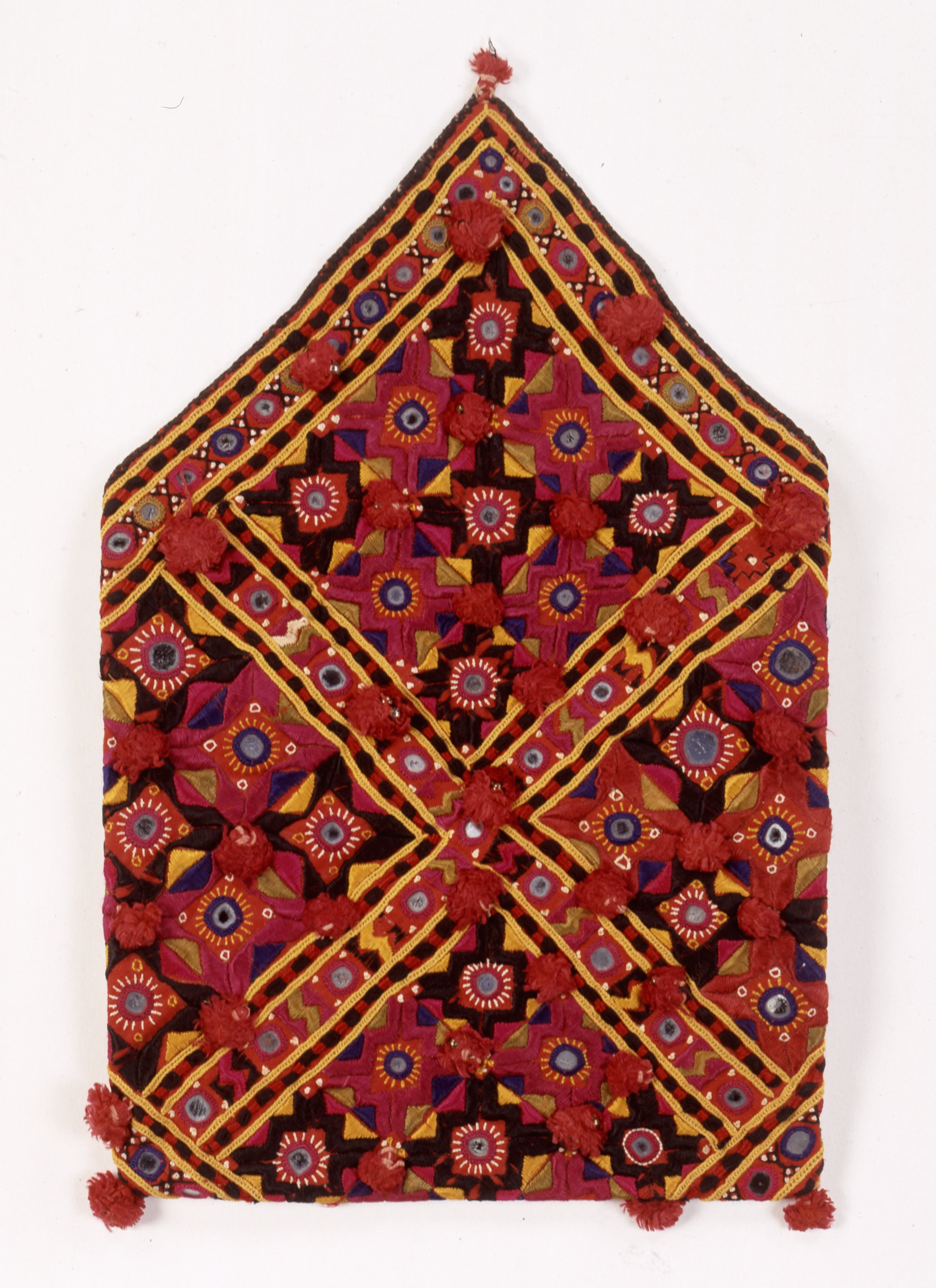 Folded bag made of cotton and heavily embroidered with silk thread. Made in Kutch, Gujarat, India.