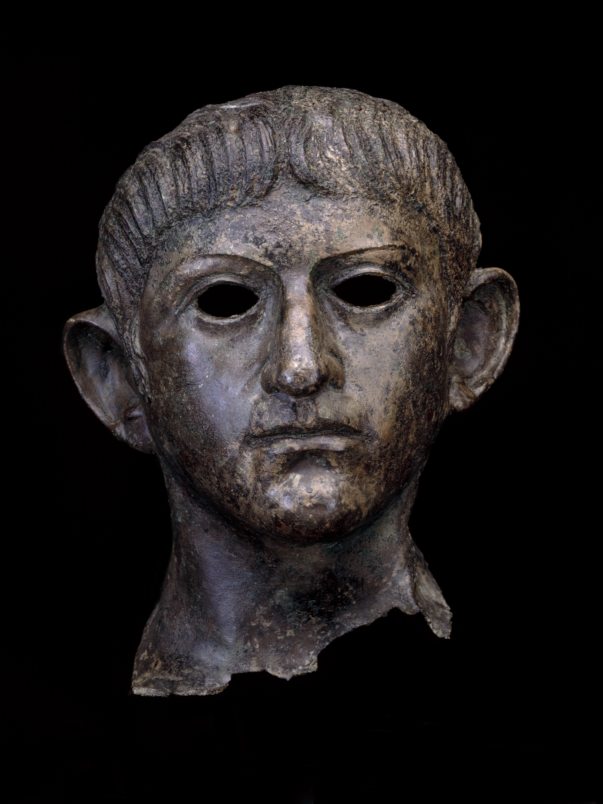 Dark brown copper head of the emperor Nero, with hollow eyes and sticking out ears looking at the viewer.