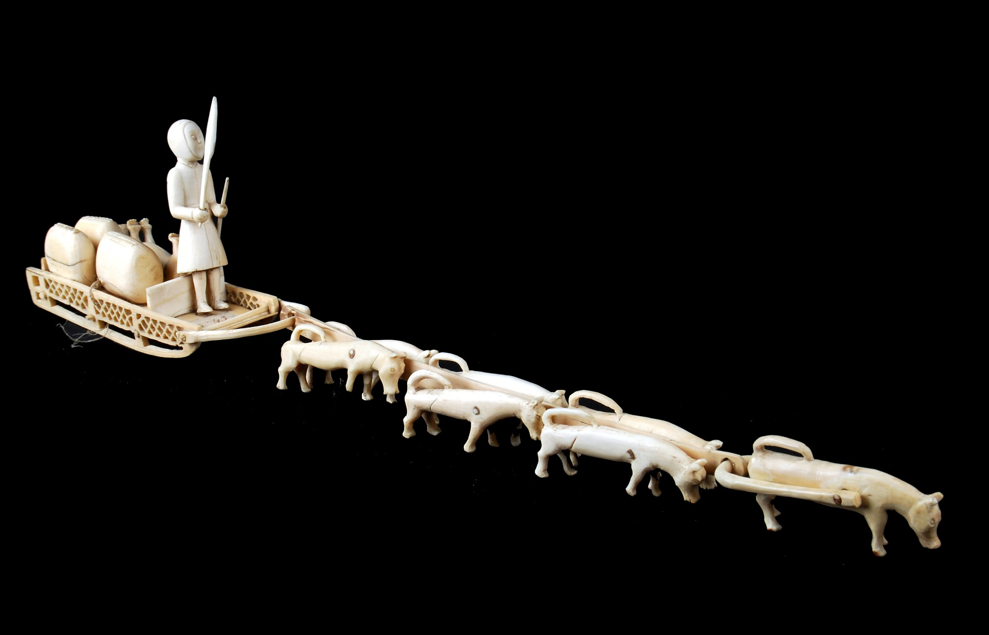 A ivory model which shows a man standing on a sled pulled by seven dogs, which are all harnessed together. On the sled are goods that are being transported as well as a dog who may be injured or dead.