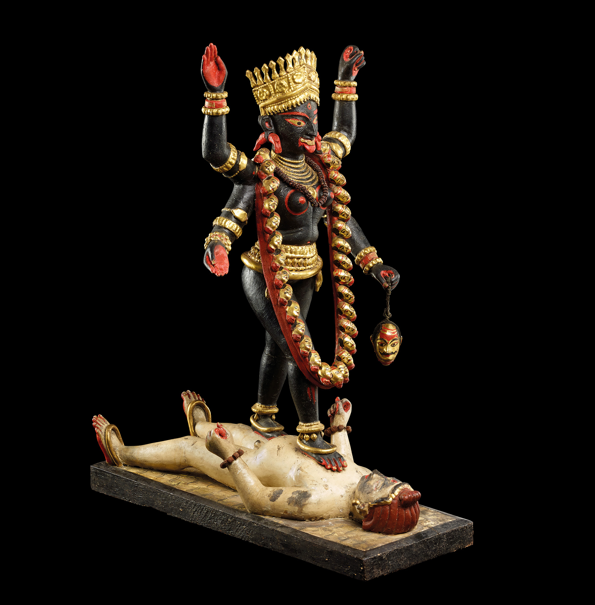 Sculptire of the goddess Kali striding over Shiva, who lies on the ground. Kali wears a gold crown and a garland of severed heads.