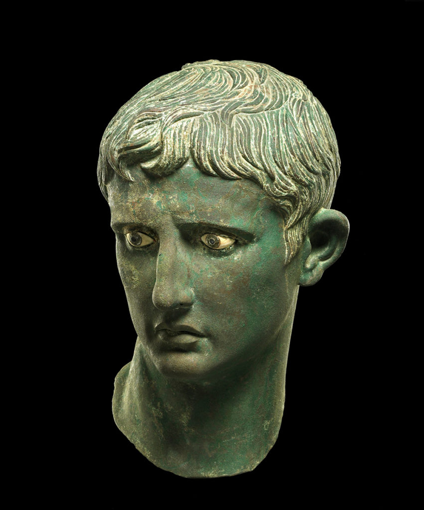 A bronze head depicting the Roman emperor Augustus with cropped hair and a downward gaze.