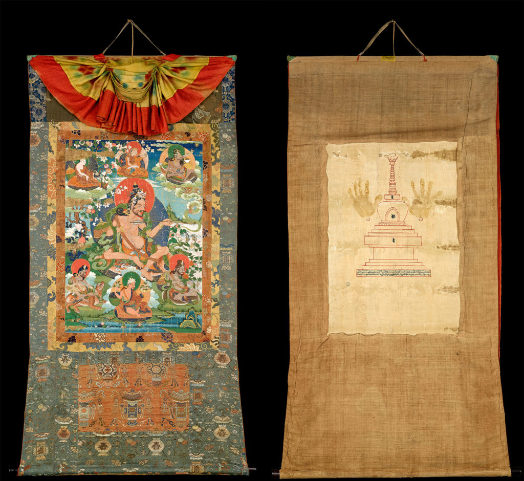 A photo of the front and back of the thangka. The front is brightly coloured and features strong patterns, and the central scene with six smaller figures and a larger figure in the centre. The back of the thangka is straw-coloured and features handprints in the centre, and the outline of a building.