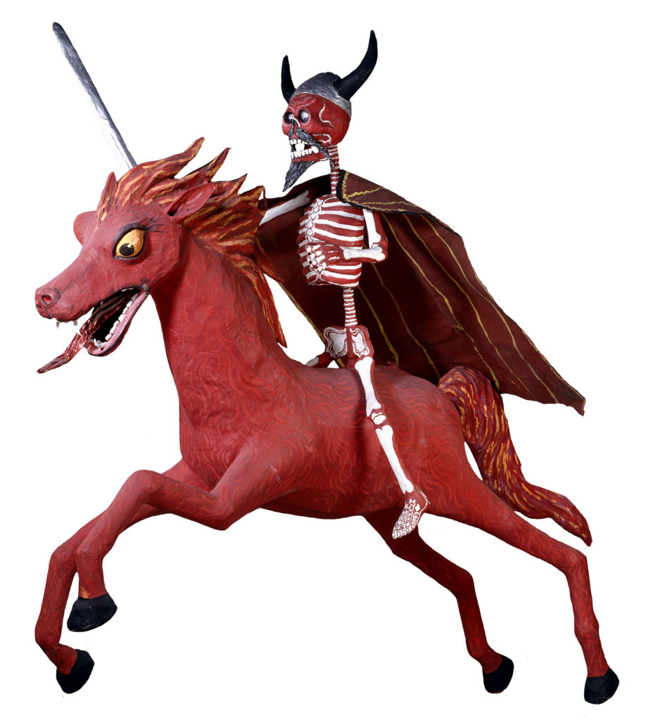 A papier mache sculpture of a red-and-white skeleton wearing a horned helmet and cape, riding a red horse with flaming hair.