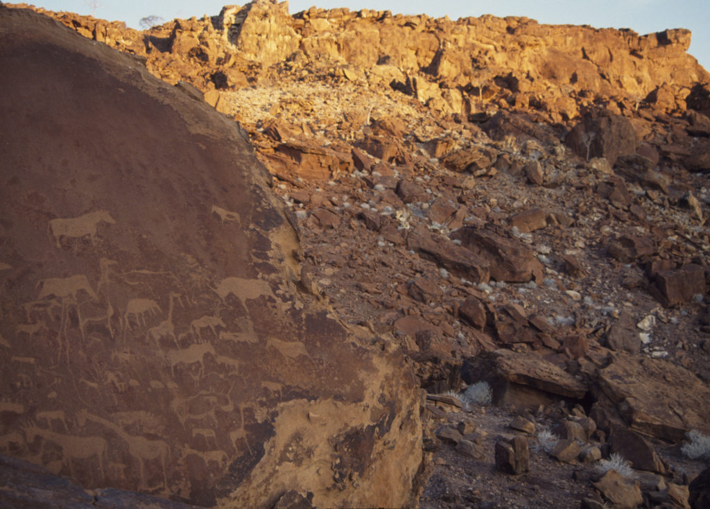 A photograph showing a rocky outcrop in a dry, red stone landscape. The view focuses on rock art of large animals including giraffes and rhinos on an outcrop on the left.