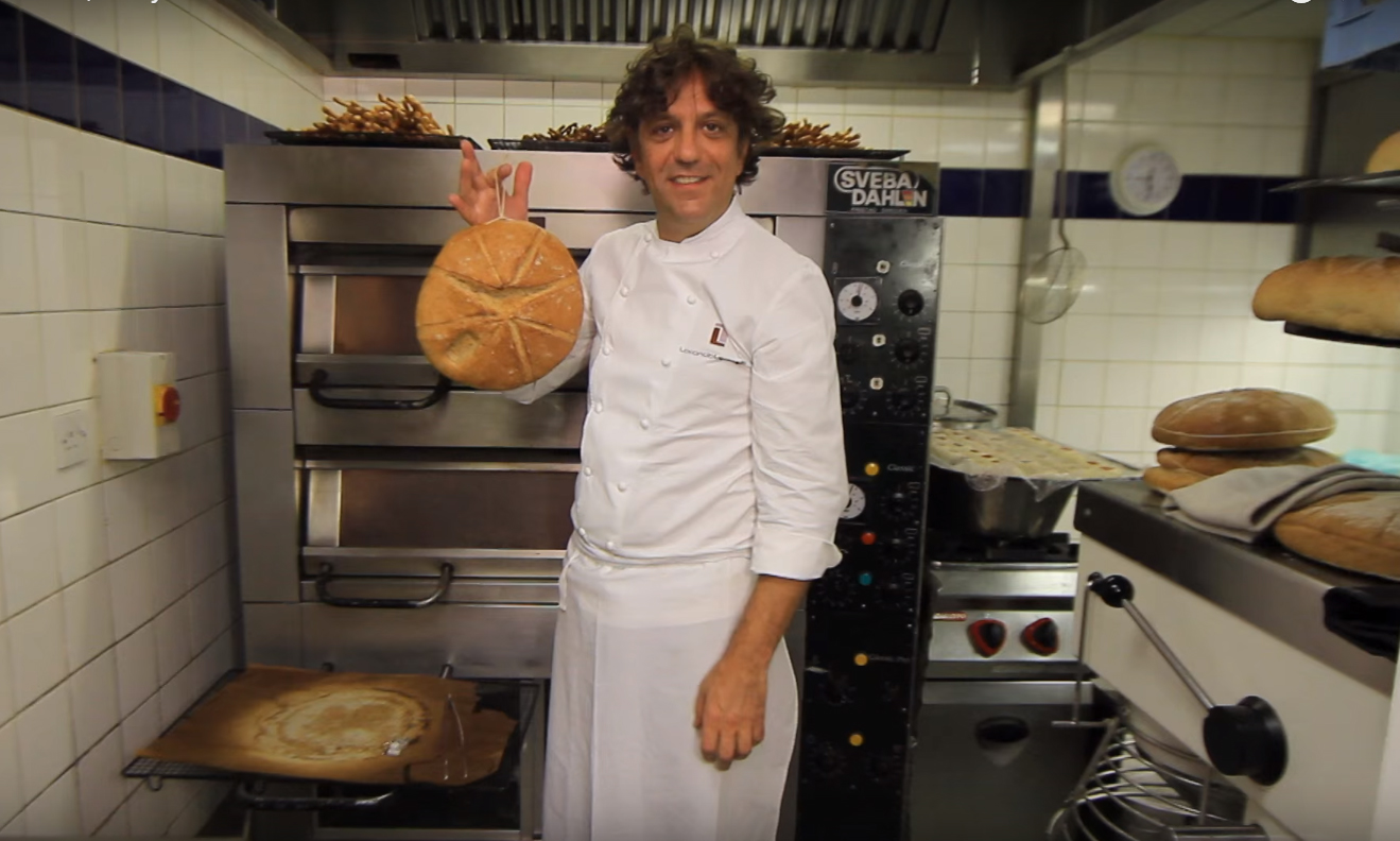 Chef Giorgio Locatelli holds a round loaf of bread in a professional kitchen.