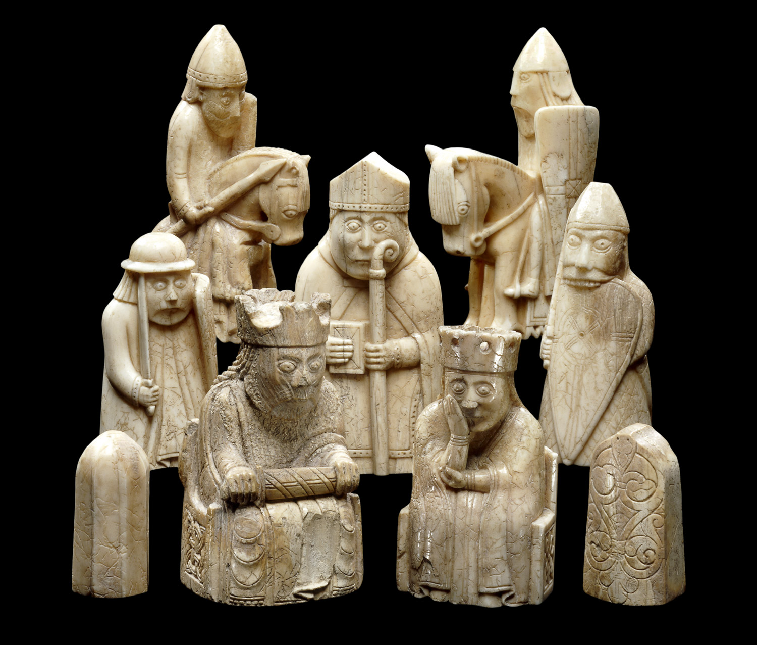 Photograph of a small group of the Lewis Chessmen, on a black background, with characterful individual expressions.