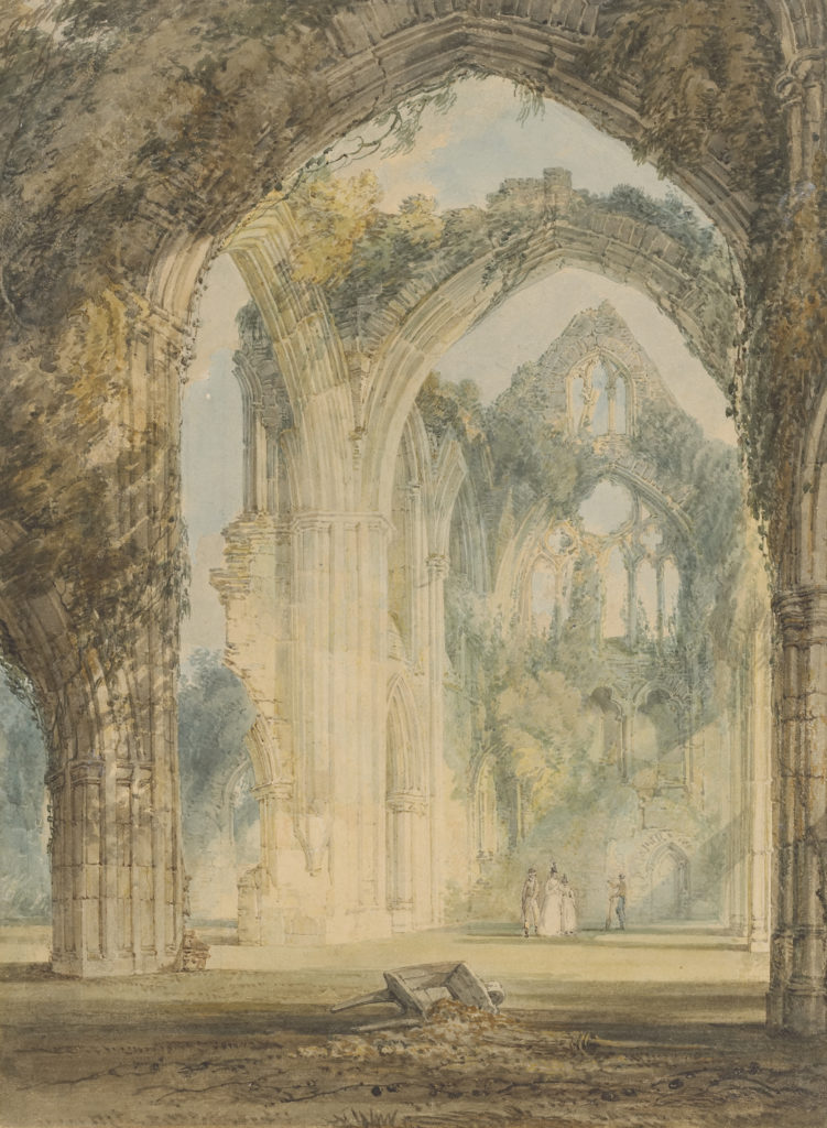 A sunny watercolour view of the ruins of Tintern Abbey. Large Gothic arches loom above a small group of men and women gathered on the grassy floor of the abbey. The roofless structure is overgrowth with foliage, and light streams in through the empty windows. A wheelbarrow lies discarded in the foreground.