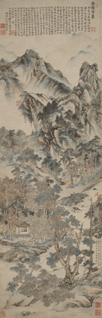 A painted scroll that depicts a wooded mountain scene in a palette of greens, blues and oranges. The long image begins with finely detailed trees and plants in the foreground, rising up to a small building where a man reads. Further up, the trees emerge from the jagged mountain, and at the top a mountain range is suggested in mist behind the main peak.
