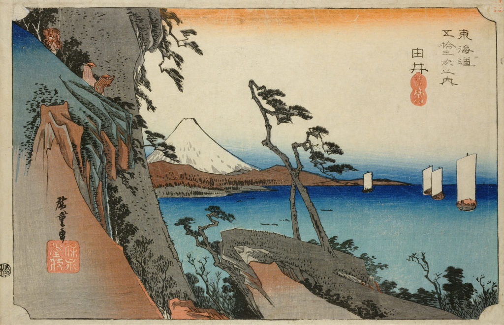 A colour print of a coastal scene. On the left, a cliff-face where three figures are seen. In the foreground, an outcrop has two woody trees which frame a snow-capped Mount Fuji in the background of the print. On the right, sail boats float on the calm blue sea.