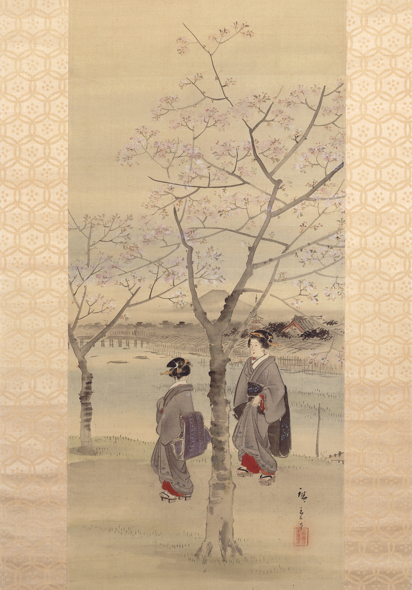 A painted hanging scroll depicting two women beneath cherry trees by a river. The trees have pink blossom. A  townscape and mountain trail away into the distance.