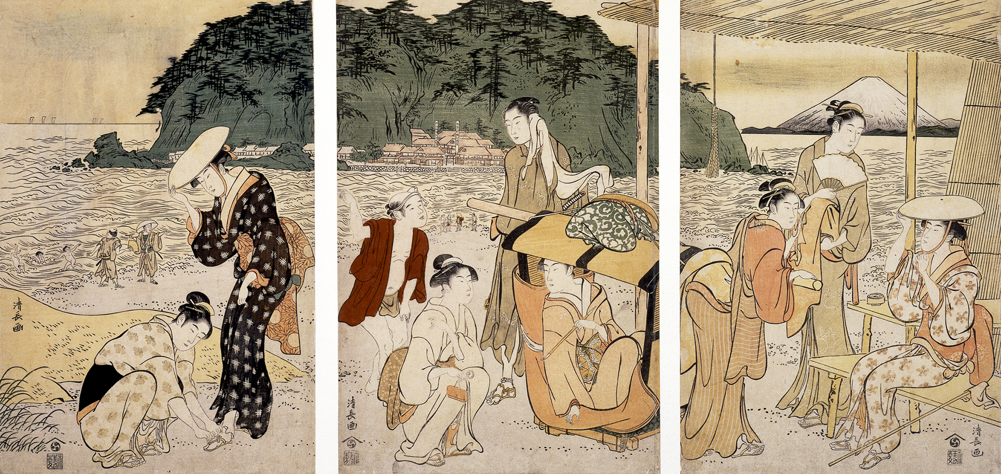 A colour woodblock print (triptych) showing a beach scene where people are relaxing and sitting on the sand. In the background, a green island rises out of the sea and a mountain looms in the distance.