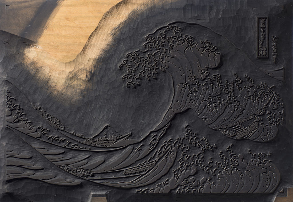 A photograph of a keyblock carved with the design for the Great Wave. Dark ink has been used on its surface.