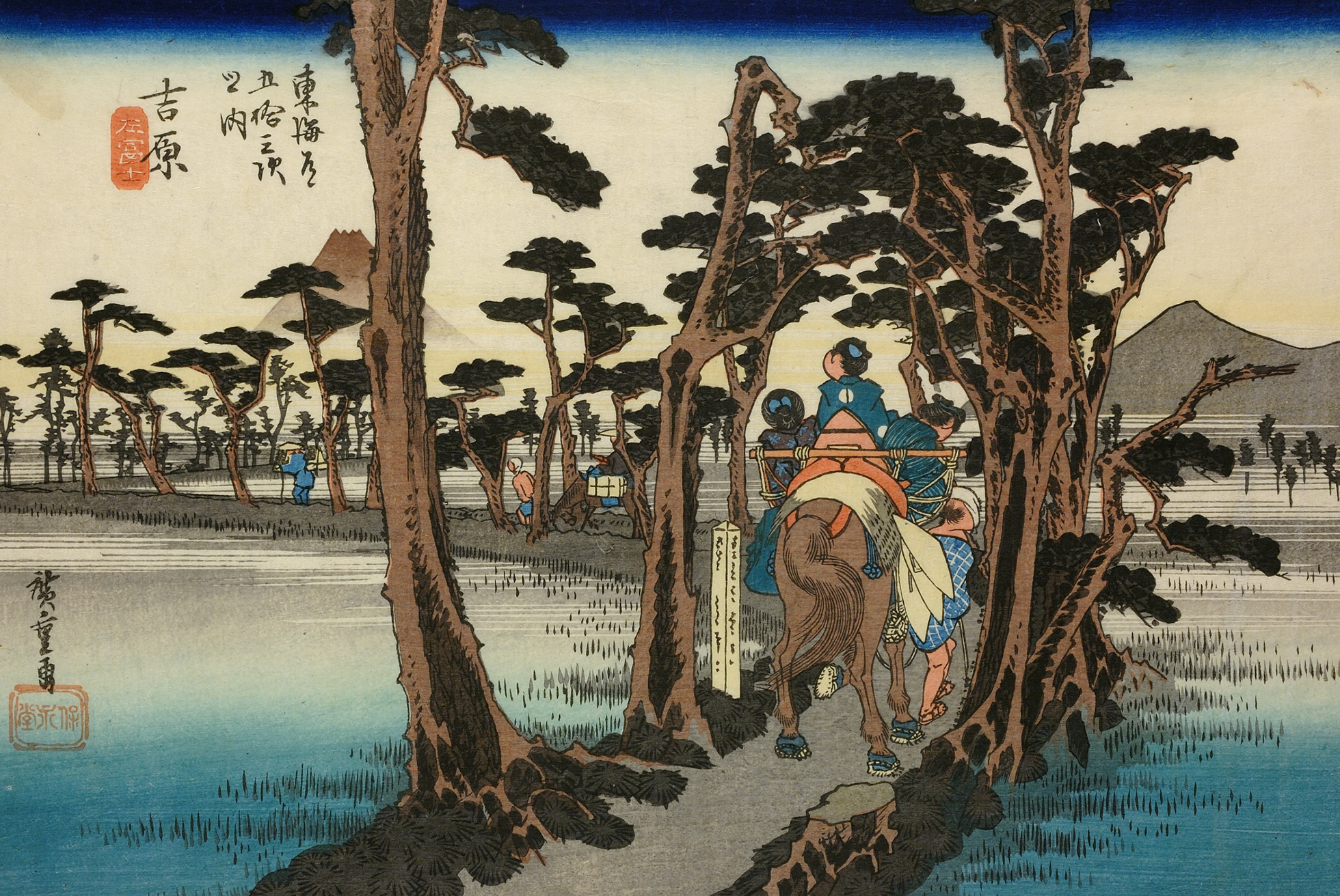 A woodblock print showing pedestrians and horse riders travelling along the Tokaido Highway. Trees line the road, with water either side. Mount Fuji is seen in the background.