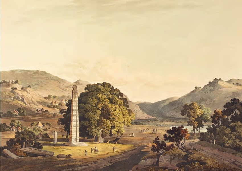 A colour print showing one of the obelisks at Aksum. The white obelisk rises high on the left side of the image. Trees and hilly landscapes around.