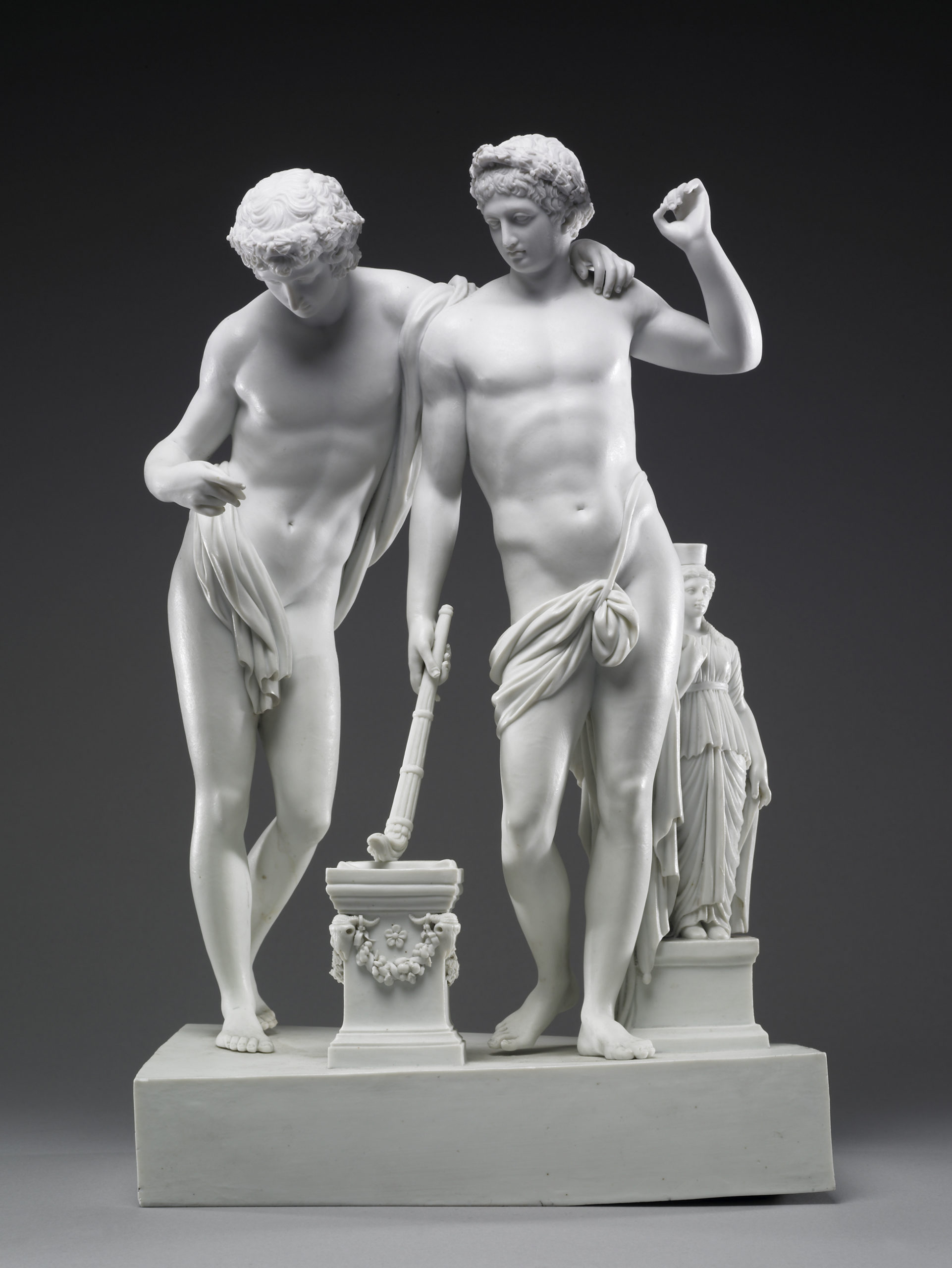 A white porcelain sculpture of the figures of Castor and Pollux. Castor (right), with his left hand raised, holds a torch against a plinth with his right hand. Castor leans casually on Pollux's right shoulder.