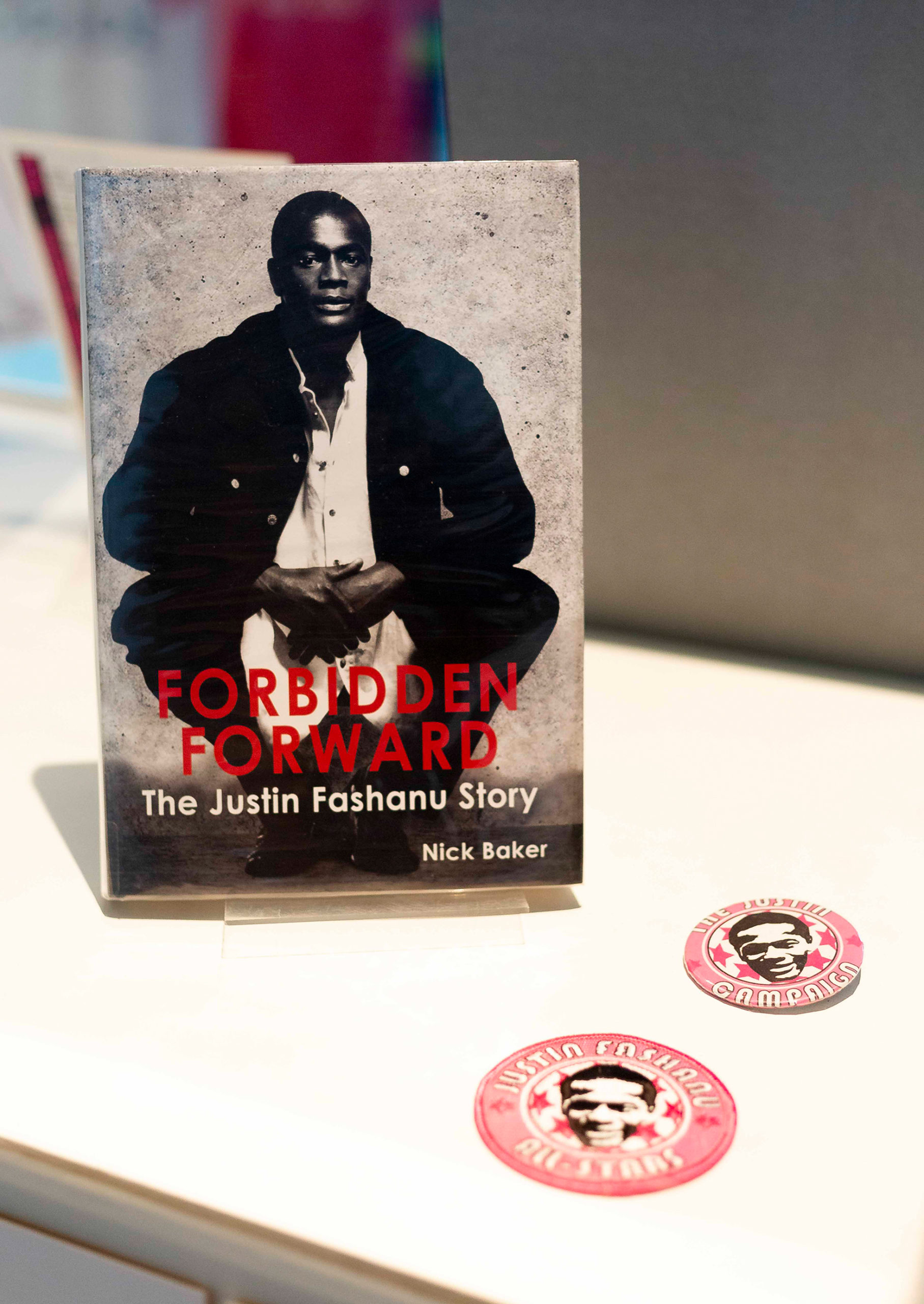 A photograph of Forbidden Forward: The Justin Fashanu Story by Nick Baker, and Justin Fashanu All-Stars fabric patch, and Justin Campaign badge.