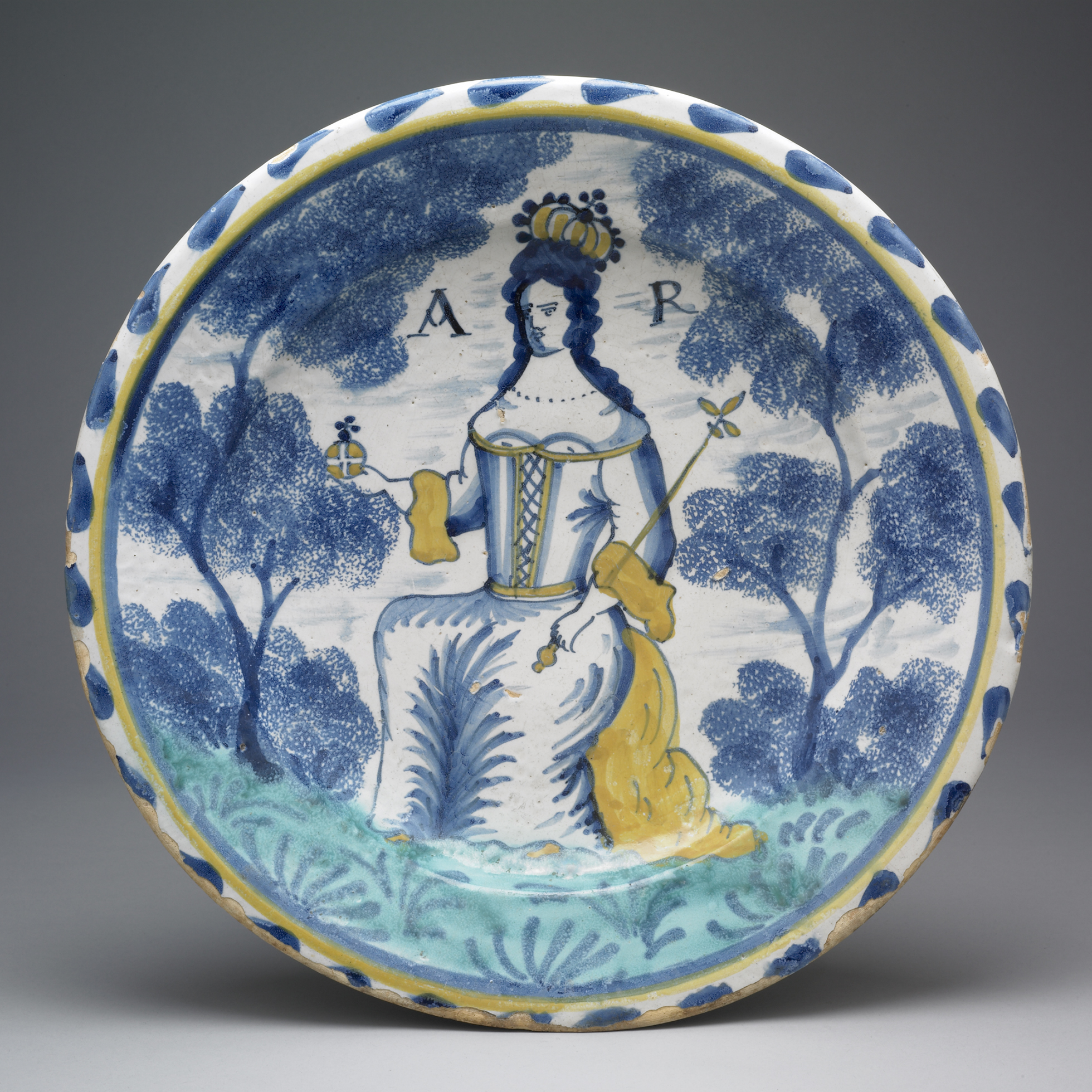 An earthenware dish glazed with blue and yellow, with a central image of Queen Anne.
