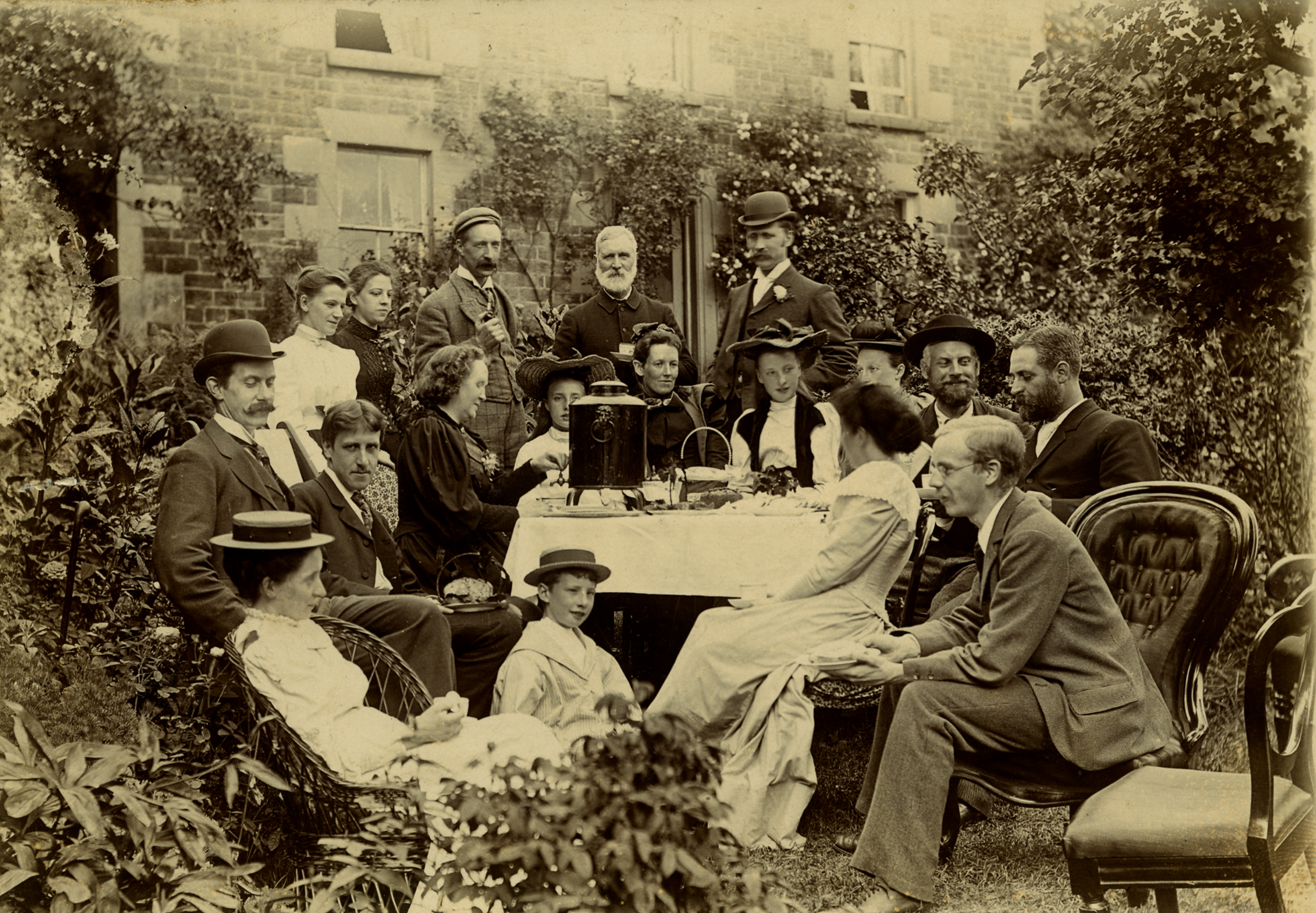 A black-and-white photograph of a group of people having a tea party in a garden setting in 1894.