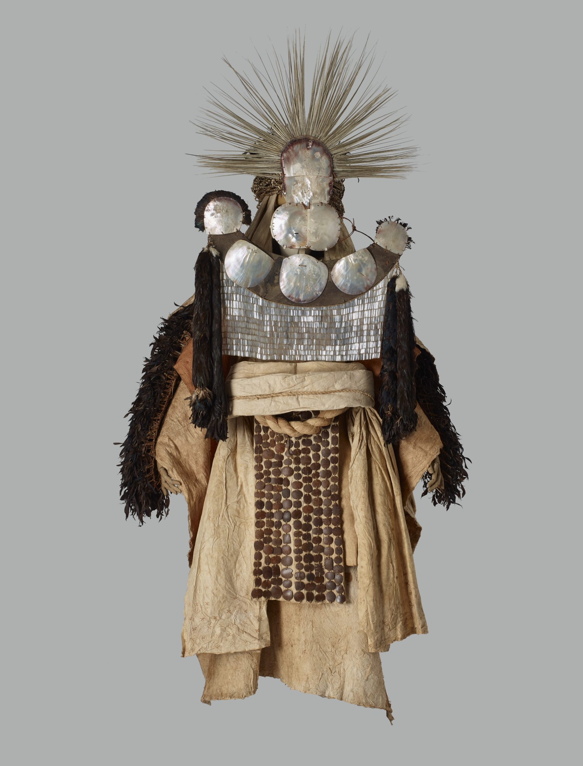 A photograph of the Tahitian mourner's costume, showing the pearl-shell and feather mask, feather cape, and barkcloth sheets.