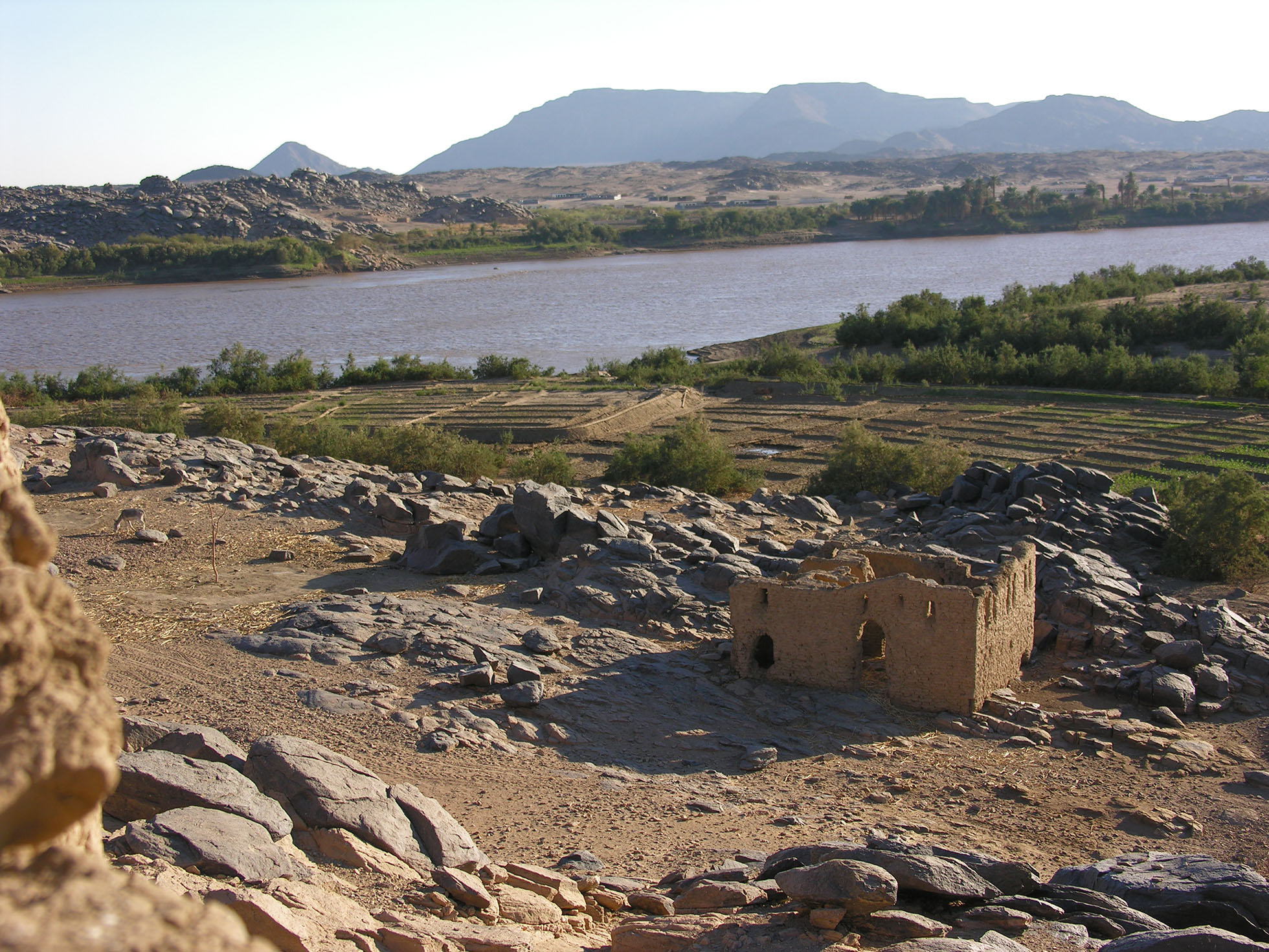 Photograph of the Kulubnarti Church within the wider landscape. The church itself is a ruin surrounded by rocks. Beyond it the cultiviation and river are visible.
