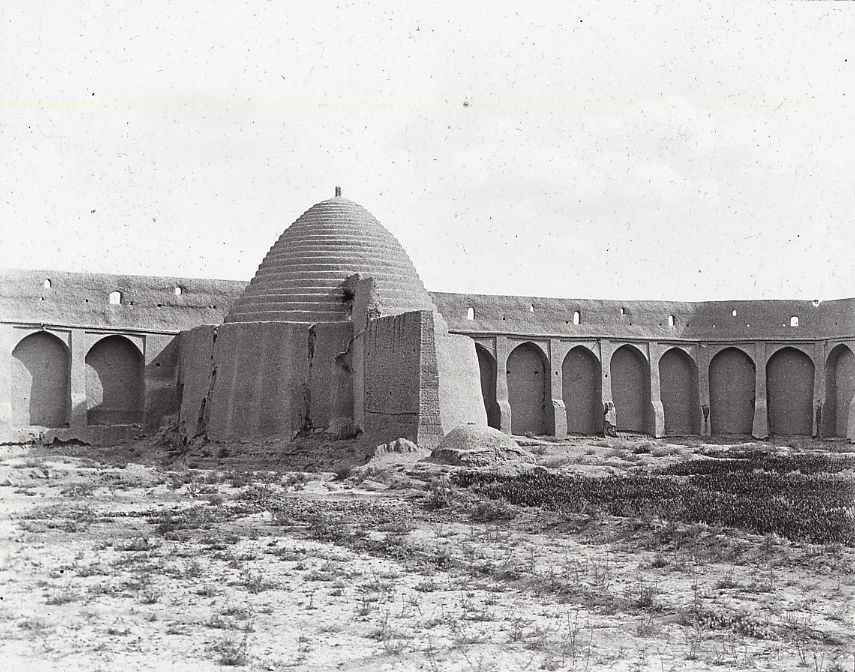 A black-and-white photograph of a large conical ice house inside a defensive wall.