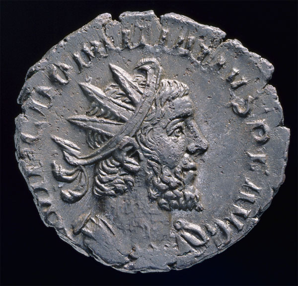 A photo of the coin of Domitianus against a black background. Domitianus has wavy hair and a beard, and wears a radiate crown.