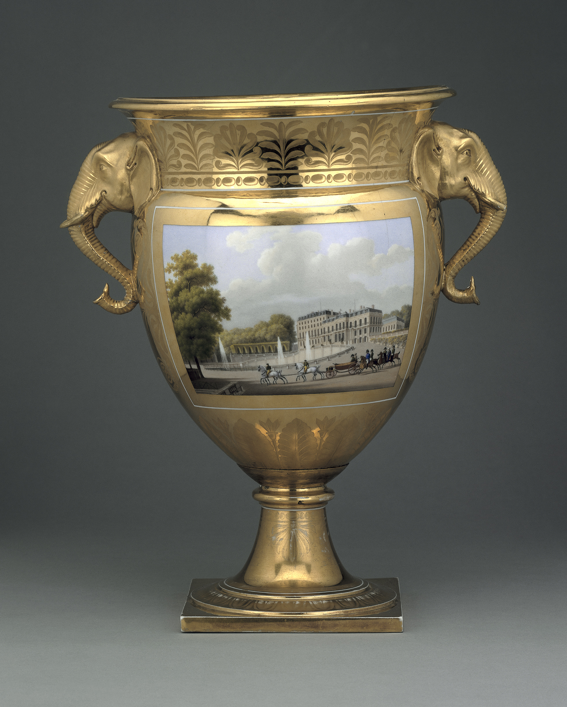 A photograph of a porcelain ice-pail, which is in the form of a large gold cup with elephant heads and trunks as 'handles'. An urban scene with buildings and carriages can be seen on the front of the object.