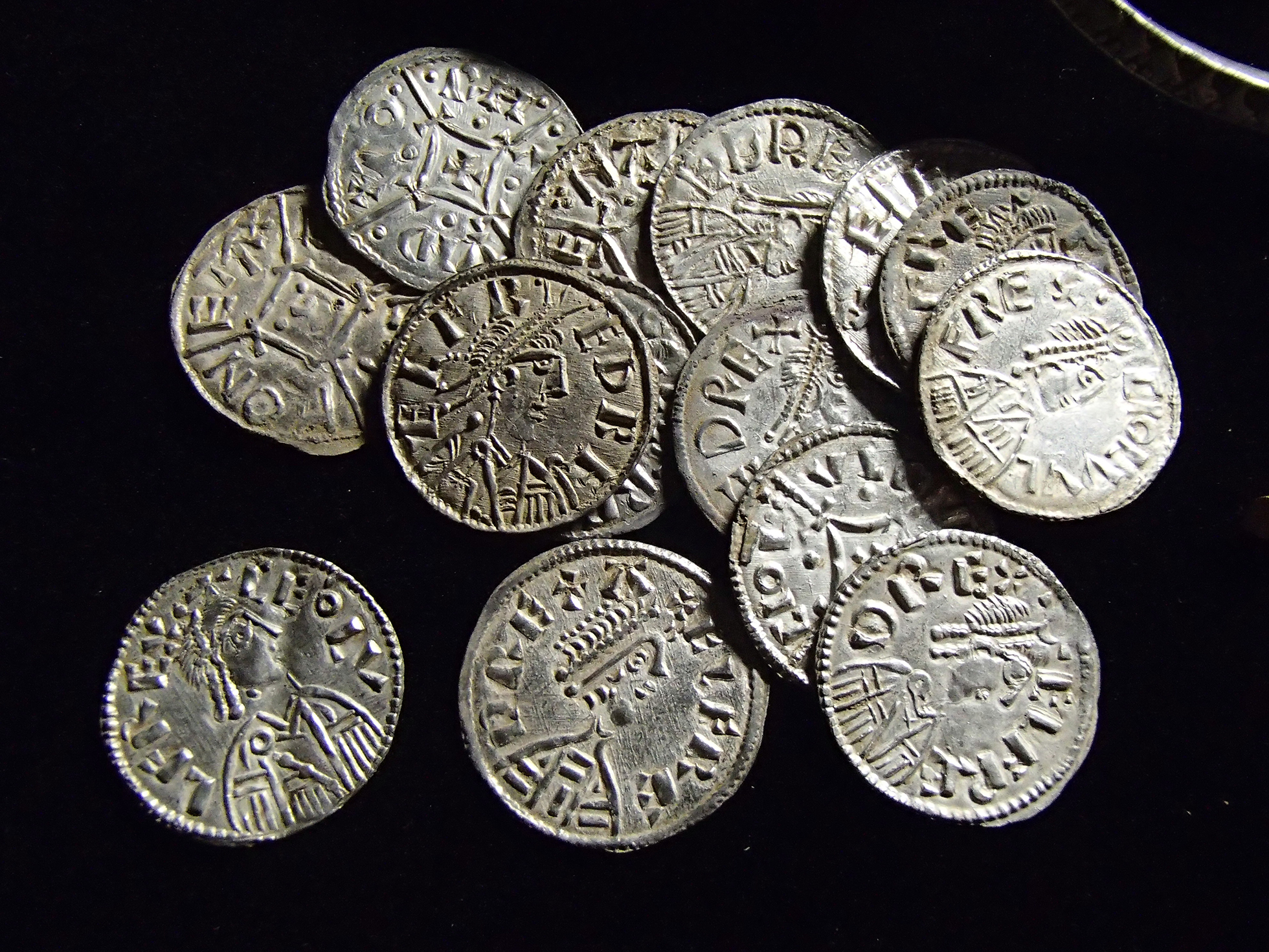 A selection of silver coins of Alfred and Ceolwulf II from the Watlington Hoard against a black background.