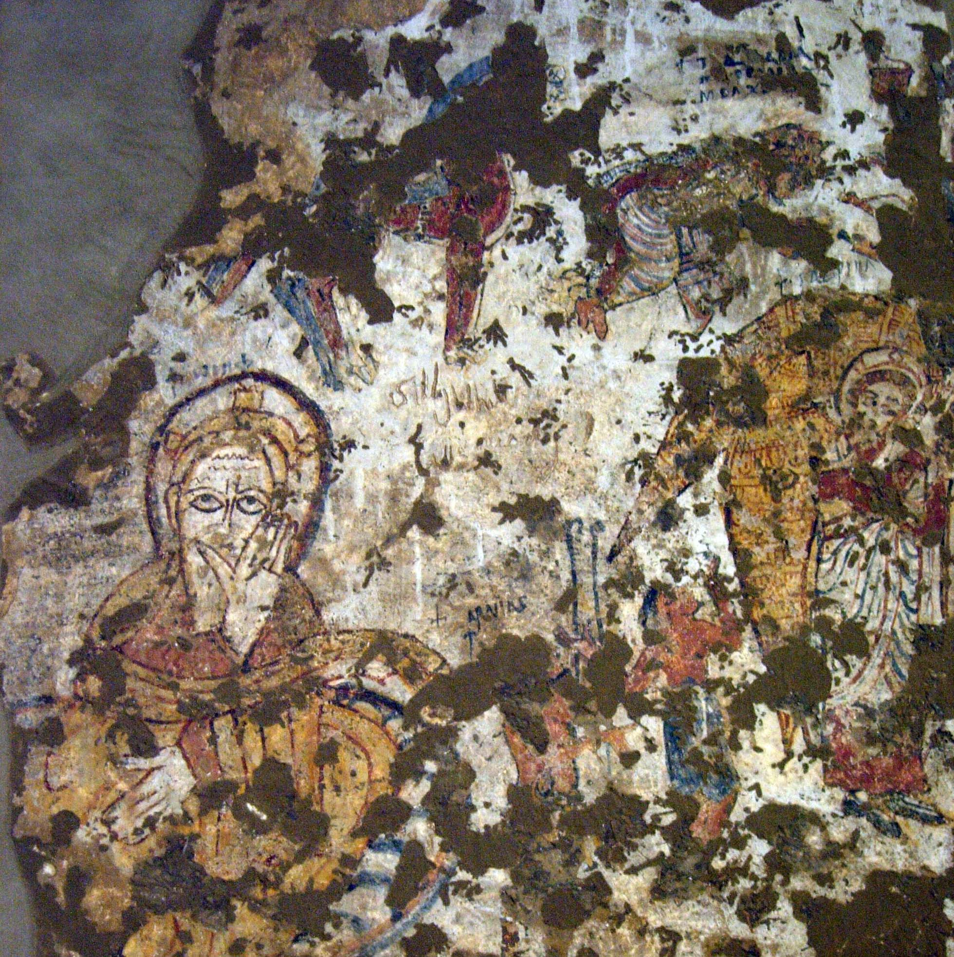 Photograph of painting on the wall of the church. The painting shows the Nativity: Joseph is on the left and an angel is on the right.
