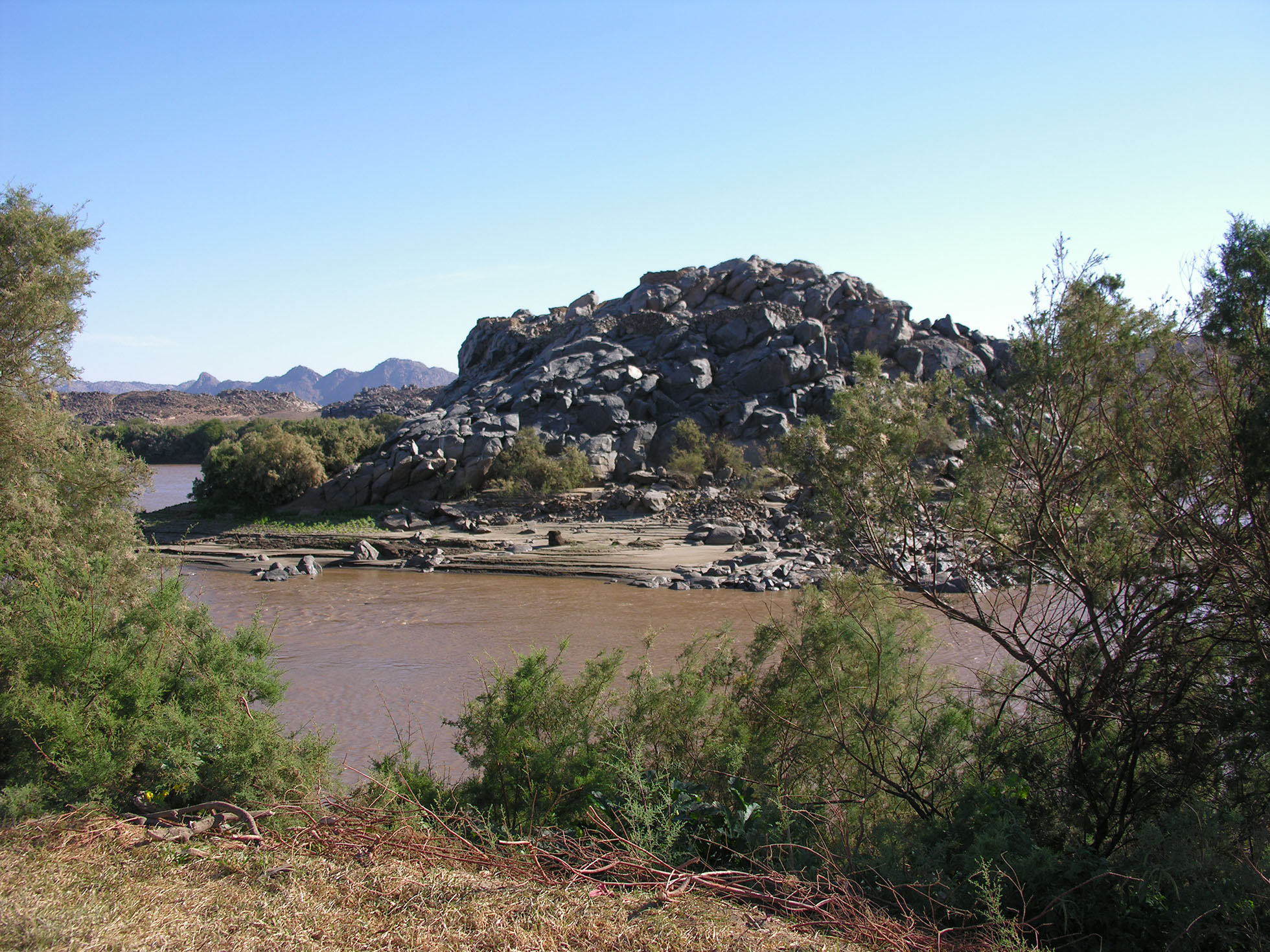Photograph of the landscape of Northeast Kulubnarti, including the river and a large rock formation.