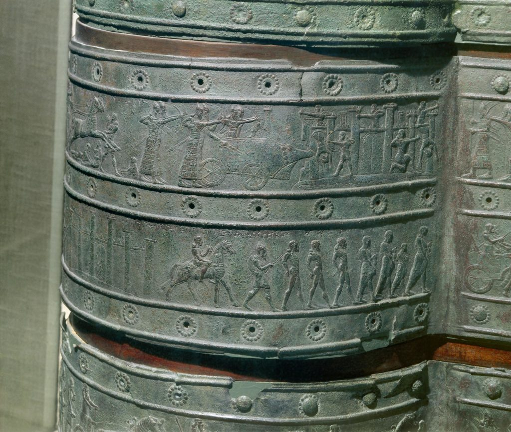 Detail of bronze band from Balawat gate showing embossed images of people.