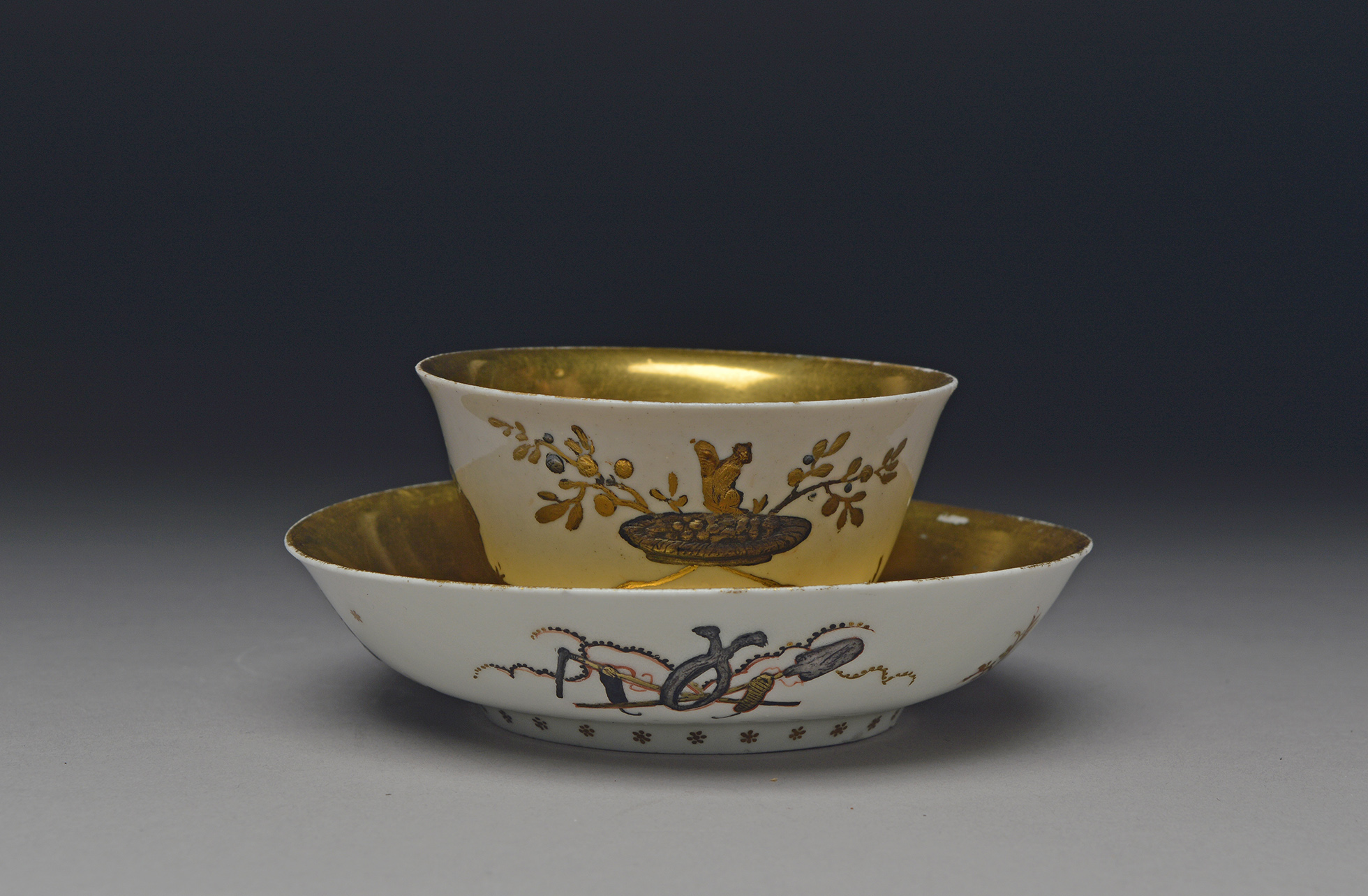 Image of a tea bowl sitting in a saucer. Both the bowl and saucer have gold interiors and finely decorated exteriors.