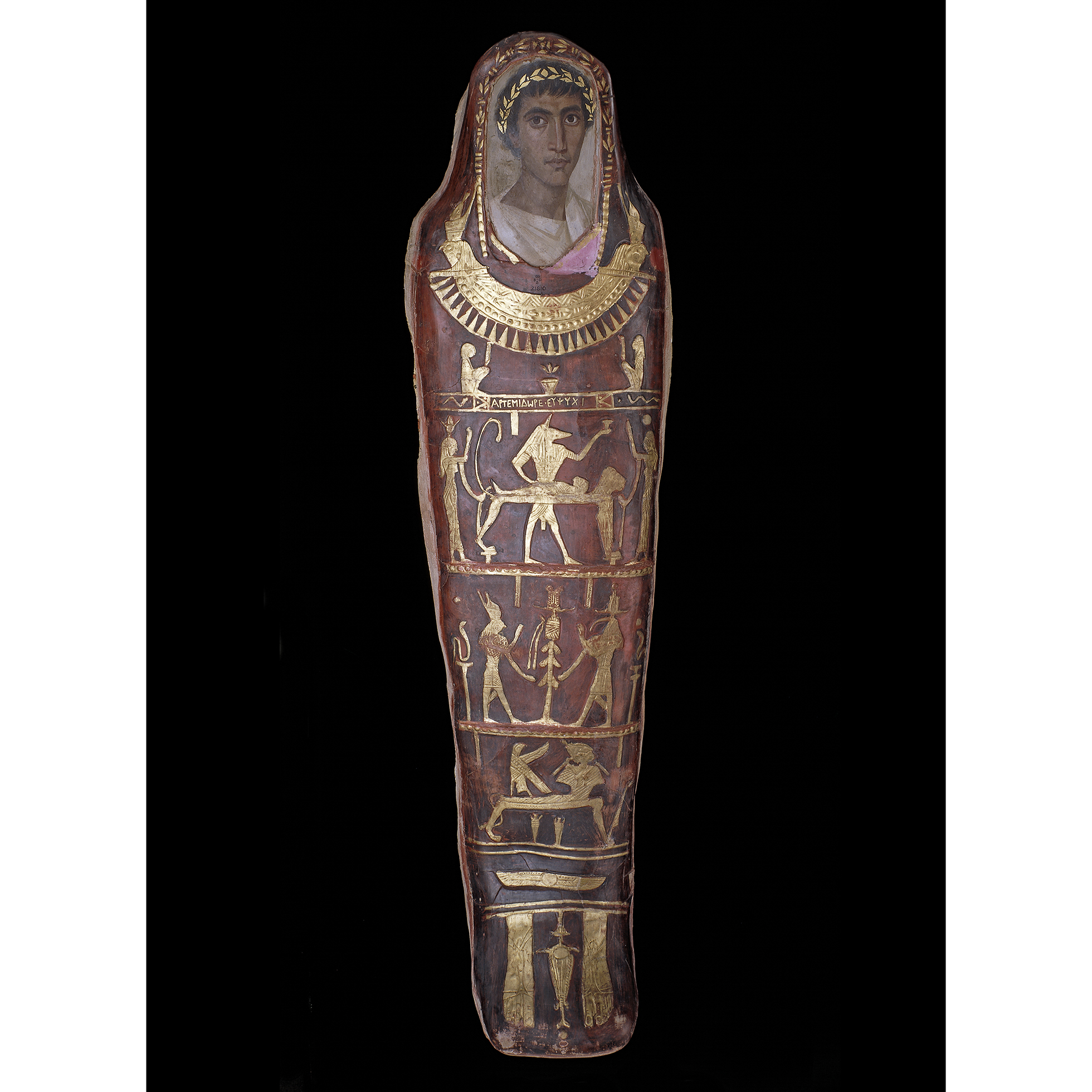 Mummy of a Greek youth, aged 19-21, named Artemidorus in a red body-case with mythological decoration in gold leaf and limewood portrait-panel covering the face.
