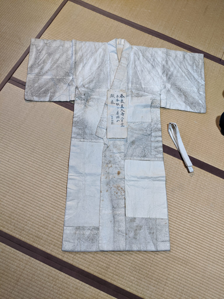 A white ceremonial robe made from paper. The white paper has been dirtied by black soot.