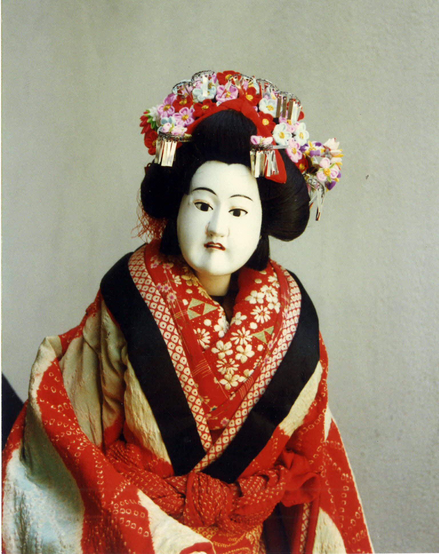 A photo of a lifelike puppet wearing red and gold ornate clothes with a formal Japanese hairstyle.