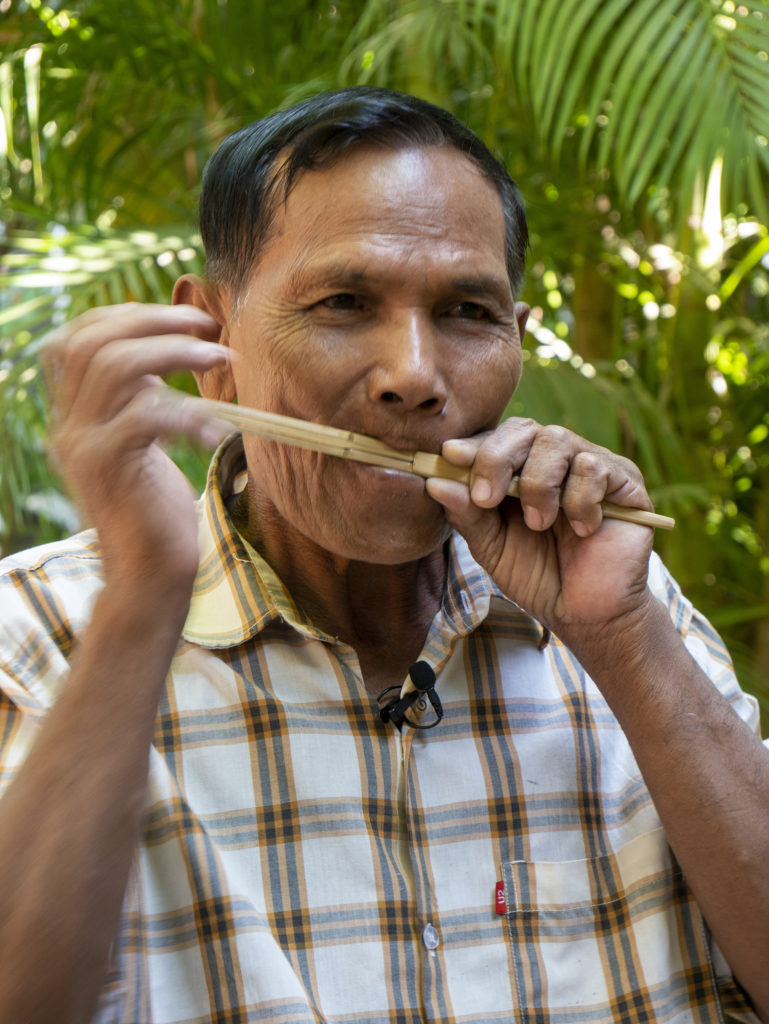 KRAK Chi playing a mouth harp. He holds the harp to his mouth with his left hand, and moves his right hand to play the instrument.