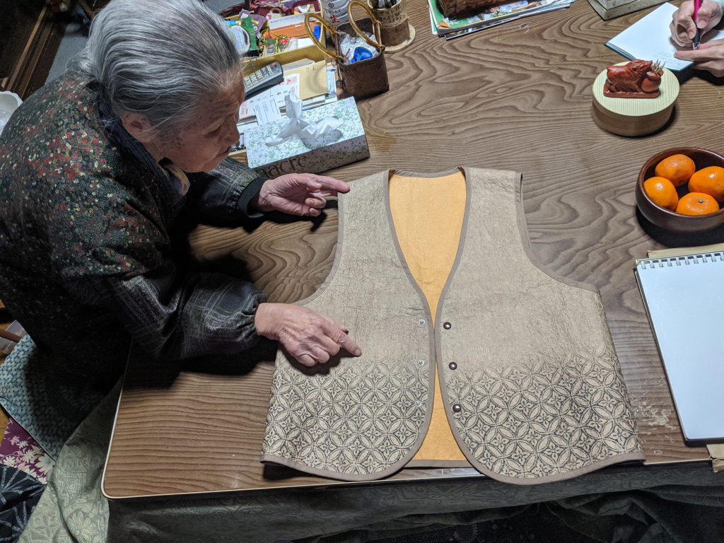 Mashiko Endō leaning over a table showing a Japanese paper vest she constructed. The vest has black floral and geometric patterns.