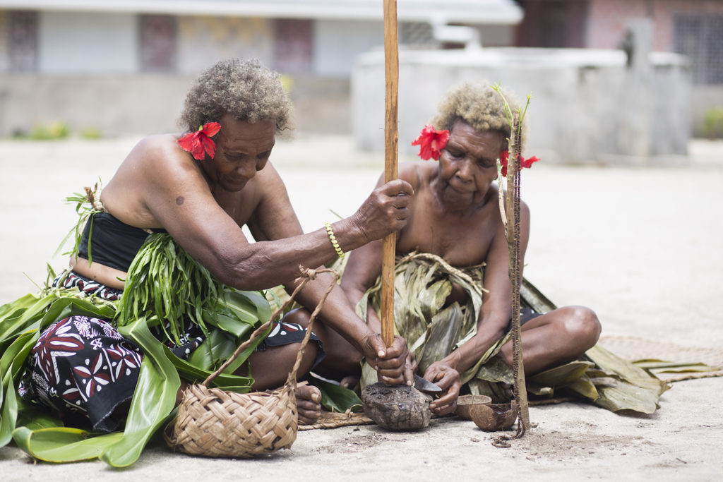 Doga and another elder make shell money while sitting on reed mats. They are using a knife and wooden tool to make the shell money.