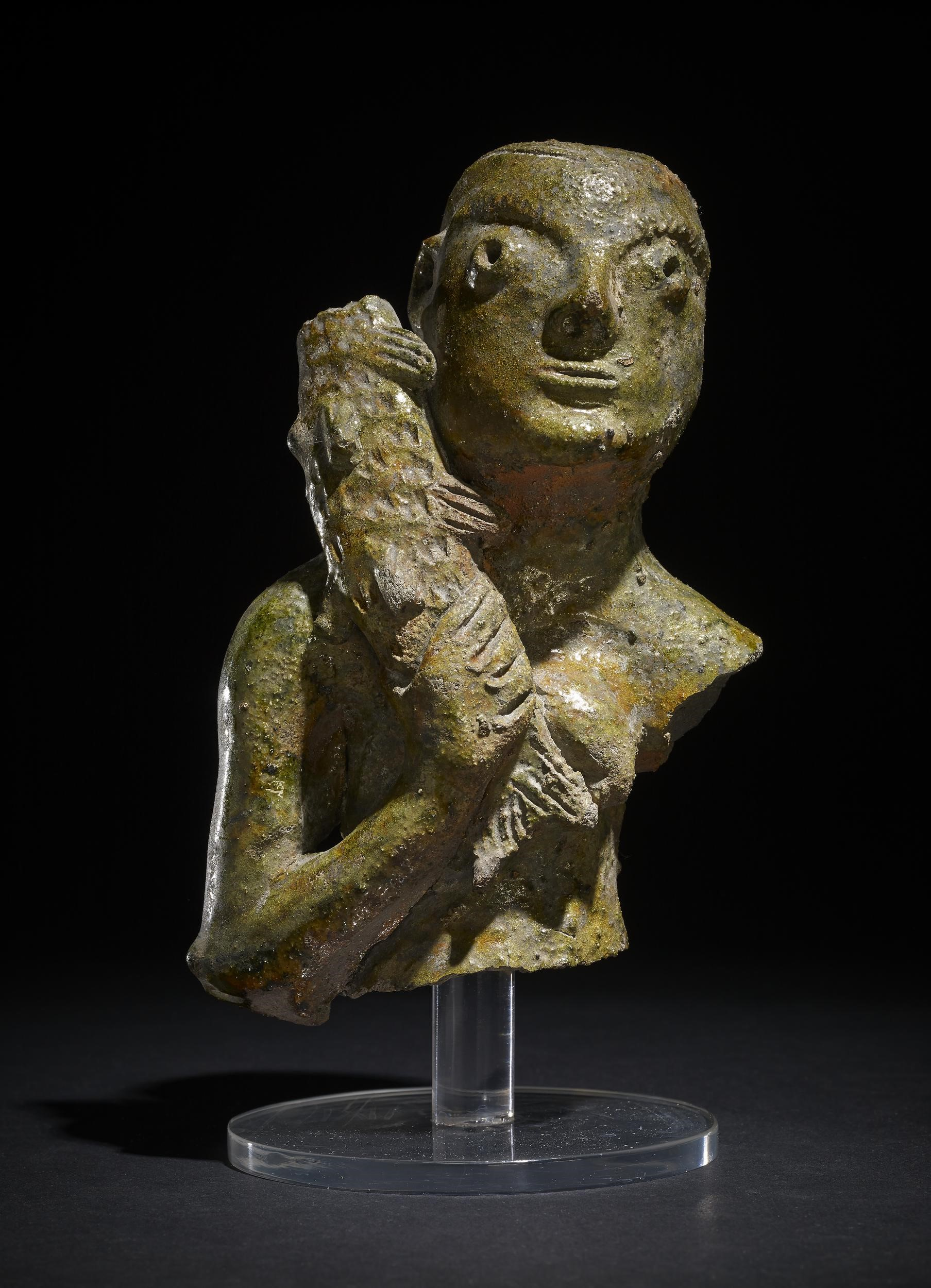 Pottery figurine with a green glaze. The figurine shows a woman's head, too and right arm. She has plaited hair carrying a fish on her shoulder.