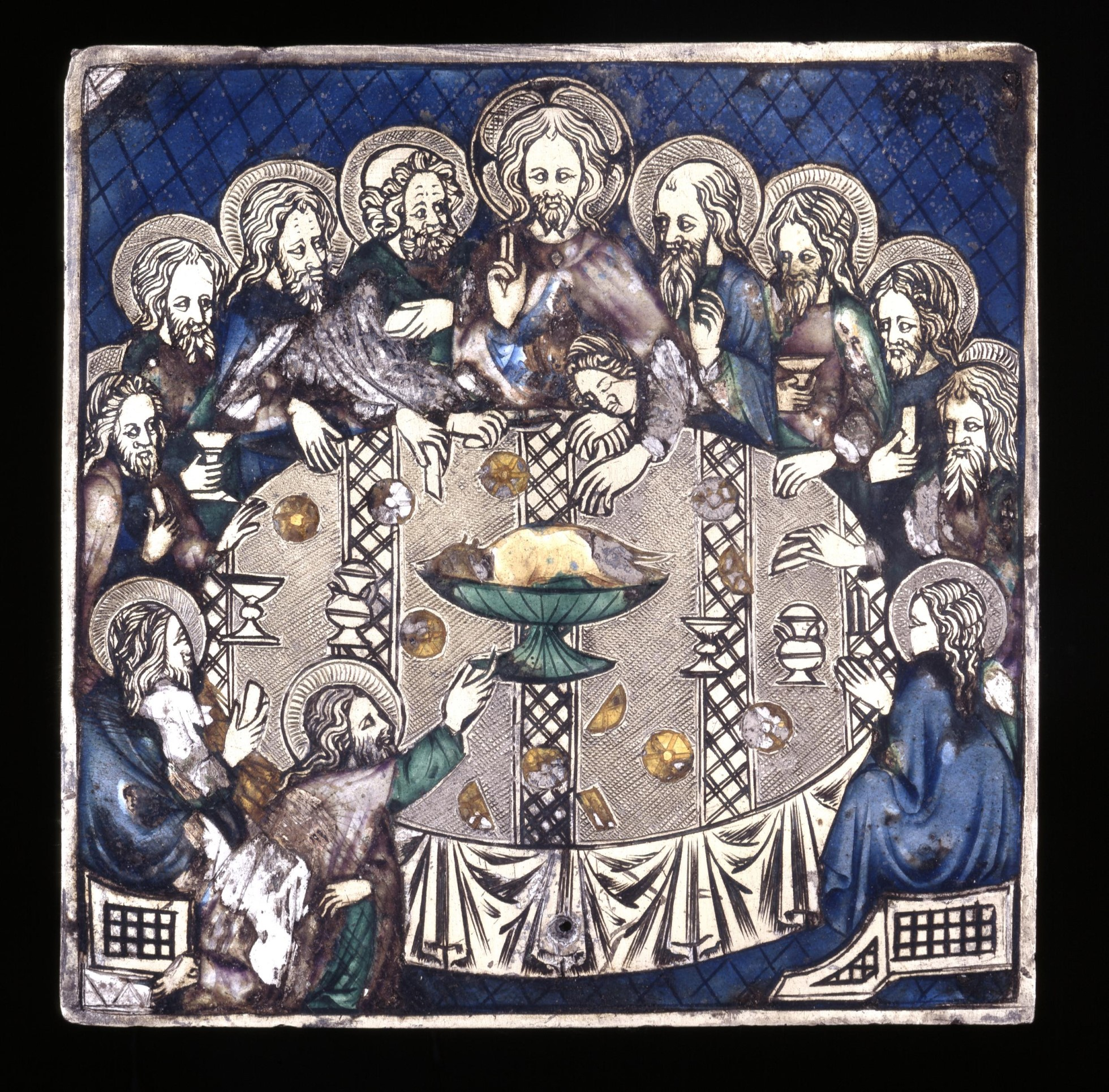 The plaque is engraved and partly enameled with translucent enamels. in blues, browns and greens. Christ and the apostles sit around a round table. In the centre of the table is a green bowl. There are various cups and vessels of different shapes on the table.
