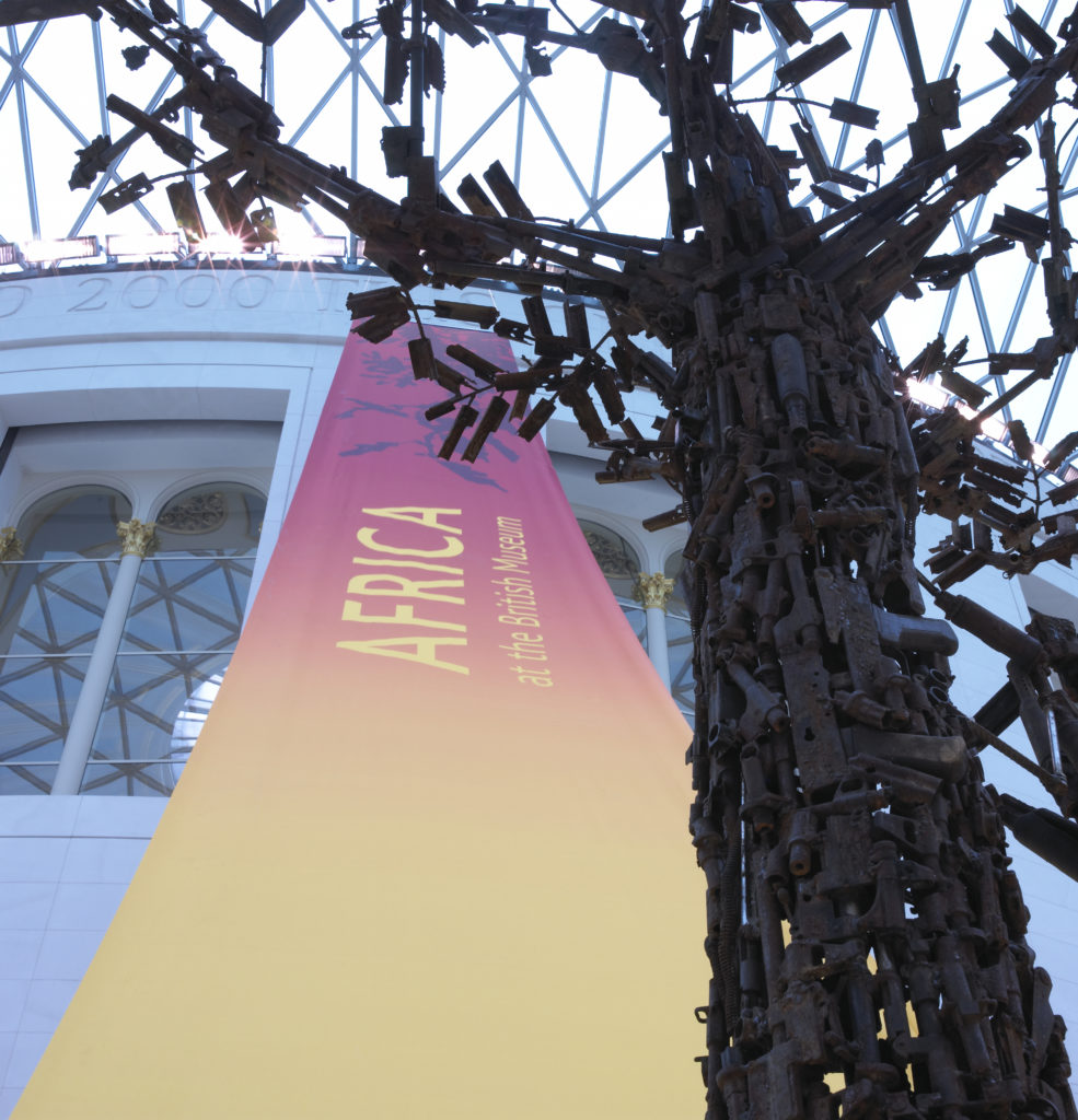 A close-up photograph of the 'Tree of Life' on display in the Great Court, with a  pink and orange banner publicising the African collection hanging behind it.
