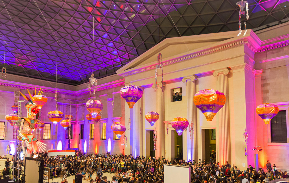 A photograoh of the Great Court with pink, purple and orange lights illuminating the space, and lanterns and skeletons hanging from the roof. A crowd is sitting below the models enjoying the celebrations.