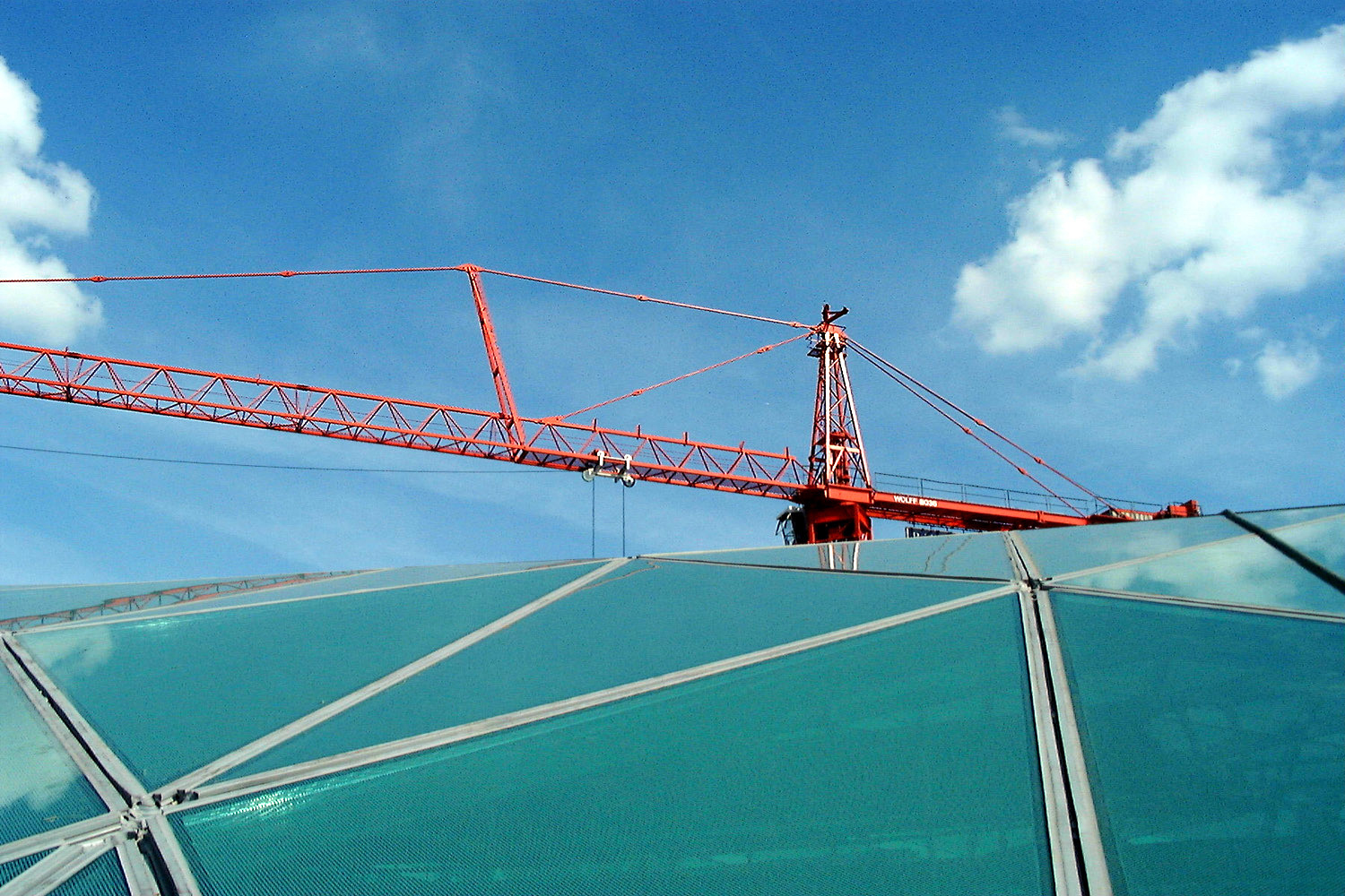 A photograph of a red crane over the roof of the Great Court, with a blue sky and fluffy white clouds beyond.