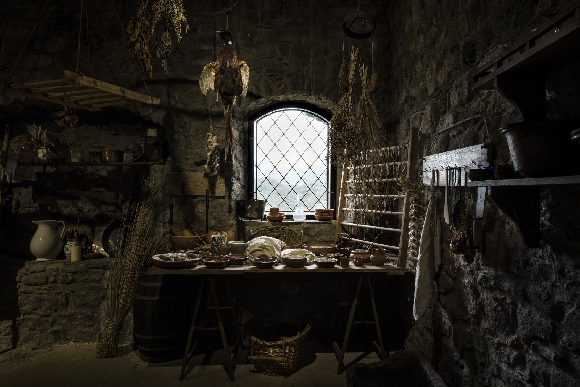 Photograph shows a dark room with stone walls. In the centre of the shot is a table with various bowls and cooking utensils below a window. In the There is rack on the right hand side. Below the table is a basket. Hanging from the ceiling are various dried herbs and a pheasant. To the left a grey jug a copper pot and other equipment sits on shelves.