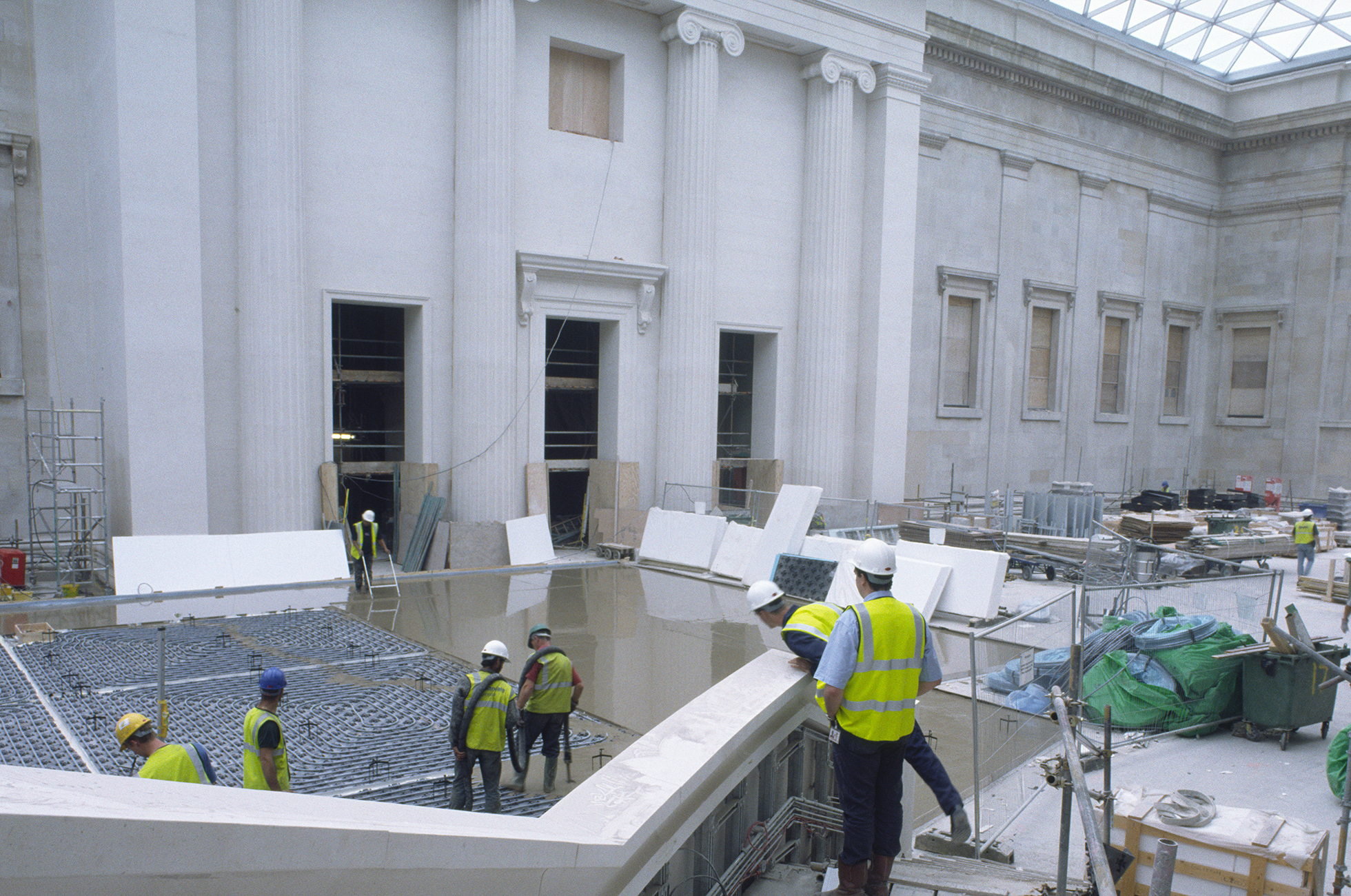 Builders wearing high-vis vests stand on the steps around the Great Court, as the flooring is prepared,  concrete is being levels, and white slabs of limestone sit waiting to be laid.